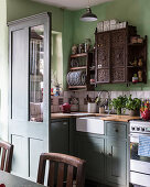 Marquetry cabinet and plate rack above sink in kitchen