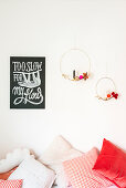 Two golden metal rings with decorations and candles next to motto poster
