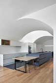Dining table next to island counter in modern kitchen with vaulted ceiling