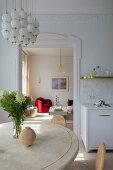 Runder Holztisch in der Wohnküche, Blick ins Wohnzimmer
