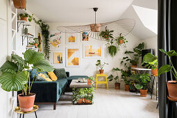 Many foliage plants, sofa and designer lamp in the living room