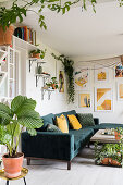 Many foliage plants, modern art on the wall and sofa in the living room