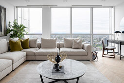 A beige corner sofa in front of a window in a living room with a panoramic view of the city