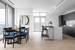 Blue upholstered chairs at a dining table in front of a modern open kitchen