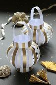 Selbstgemachte Laternen aus gestreiftem Papier in Gold und Weiß