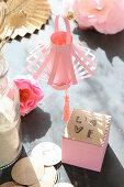 Rosafarbener Lampion aus Papier und Würfel mit Love im Sonnenlicht