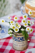 Place a glass inside a tin, fill with water and arrange the flowers