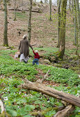 Mother and child in spring woods surrounded by wood anemones and lesser celandines
