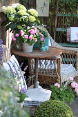 Comfortable seating area surrounded by hydrangeas, busy Lizzies, geraniums and box