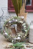 Rustic straw Easter wreath decorated with lichen, feathers and eggshells