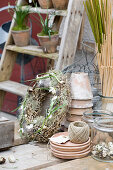 Rustic Easter wreath decorated with lichen and feathers next to craft materials