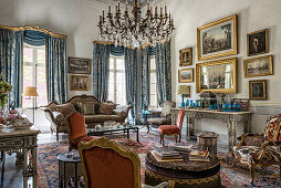 Antiques and chandeliers in opulent living room
