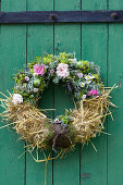Summer wreath of roses, lady's mantle, chamomile, tufted vetch, green apples and straw