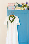 Nostalgic nightgown and a heart-shaped wreath on blue cupboard