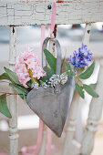 pink and grape hyacinths in a metal heart on a chair