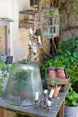 Glass bell over a plant on an old table in a garden with an assortment of objects