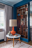 Table lamp on round side table in front of vases on partition shelving