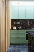 Black terrazzo elements, green cabinets and wood cladding in kitchen