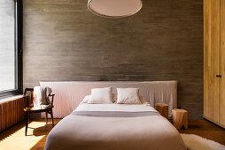 Sonniges Schlafzimmer in Naturtönen mit Betonwand