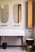 Organisch geformte Spiegel überm Waschbecken auf Möbelfüßen