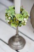 Wreath of green hydrangeas, pinecones, and snowberries