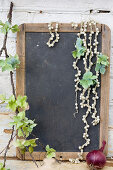 Branch with hydrangea blossoms and pearl necklaces on a chalkboard