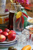 Set table in an autumn garden with apples and autumn leaves