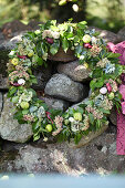 Autumn wreath made from ivy, sedum plant, hydrangea blossoms, onions, and green apples