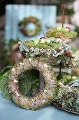Autumn wreaths made of moss and hydrangea blossoms, Brussels sprouts, and onions as decoration