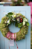 Door wreath of moss with ivy, hydrangea blossoms, and Brussels sprouts