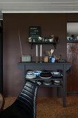 Regal und Konsole mit Geschirr vor dunkler Wand in der Küche