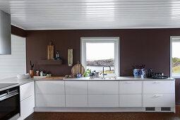 Weiße Küchenzeile vor dunkler Wand und Fenster