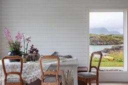 Esstisch mit rustikalen Stühlen im Zimmer mit weiß lackierter Holzverkleidung