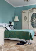 Bedroom with antique wardrobe and walls in turquoise