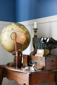 Globe, wooden box and vintage flea-market finds on small, old wooden table