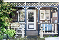 Vintage accessories on veranda adjoining house with pretty front garden