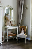 Doll on old Baroque chair and tailors' dummy on console table