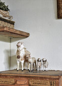 Vintage-style arrangement of old toy sheep on top of antique wooden trunk