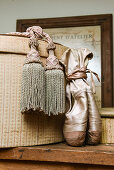 Tassels and ballet shoes arranged next to old hat box