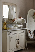 Vintage-style arrangement of doll and scales on old washstand