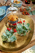 Table decorated for Christmas with eucalyptus and berry branches on golden plate