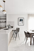 Open-plan kitchen and dining table in bright, modern living room