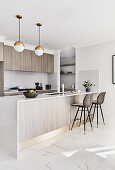 Modern, open-plan kitchen with pale grey cabinets and gold accents