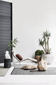 Garden lounger, plants and Boho decorations on terrace with rug