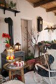 Gemütlicher Sitzplatz mit weihnachtlich dekoriertem Beistelltisch vor Kaminofen