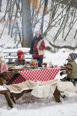 Picnic with children in the snowy forest