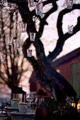 Hängende Laternen am Baum über gedecktem Tisch