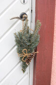 Spruce branches in chicken wire bags as door decoration