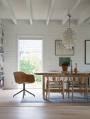 Dining table in room with white-painted wood cladding