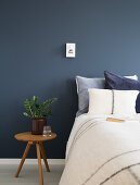 Bed and bedside table against deep blue wall
